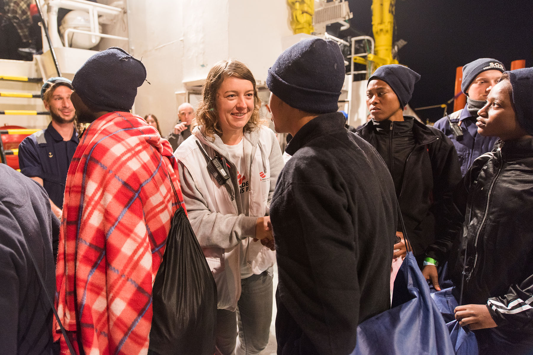 A Doctors Without Borders nurse greeting rescued people on a search-and-rescue vessel called the Aquarius.