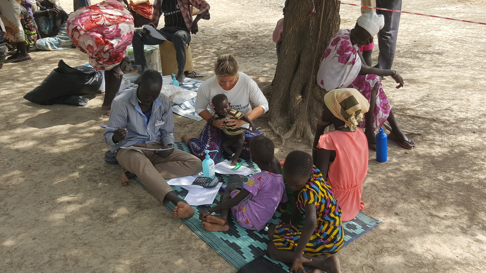 MSF staff sitting down and holding a child outdoors - surrounded by another MSF staff member and patients.