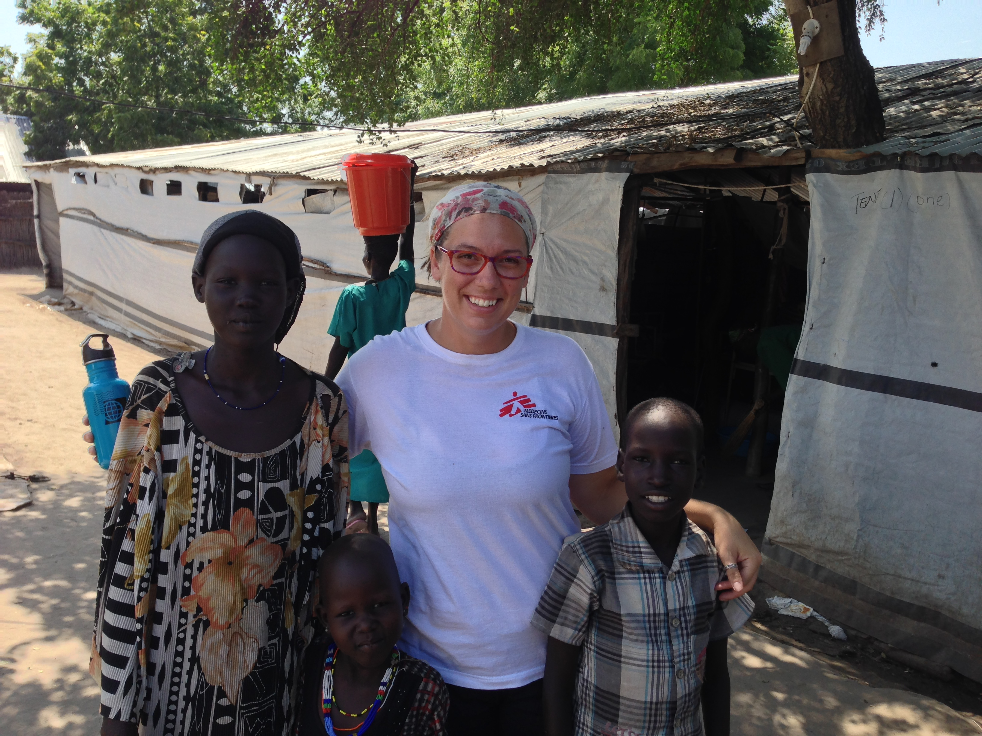 A Doctors Without Borders nurse and two patients smile for a photo.