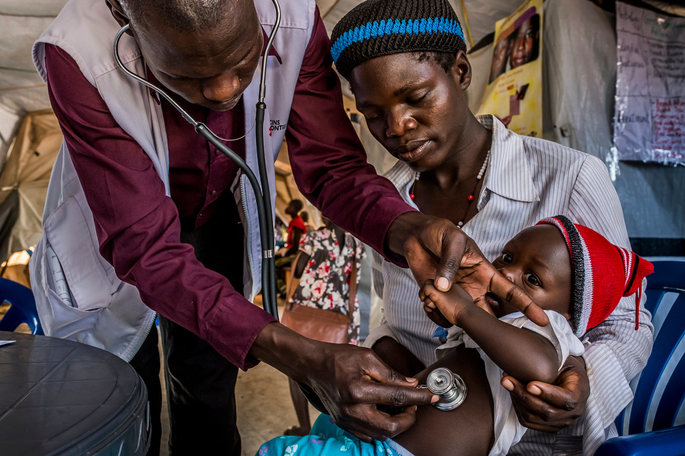 An MSF staff member examines a child using a stethoscope.