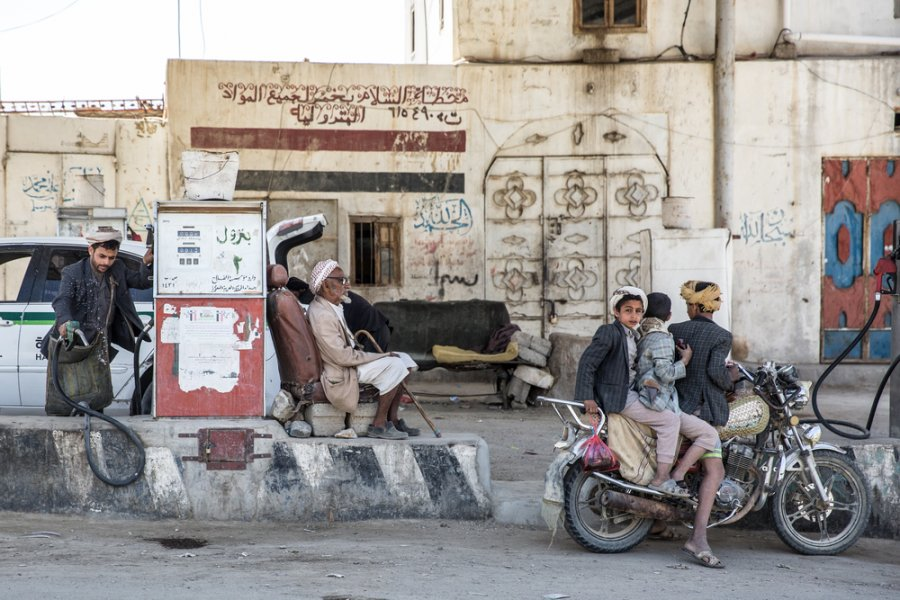 Men fill up with gas at a gas station in Khamer, in Amran governorate. Khamer, Yemen, March 2018.