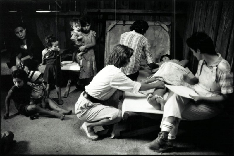 A Doctors Without Borders staff member consults Salvadoran refugees in 1981.