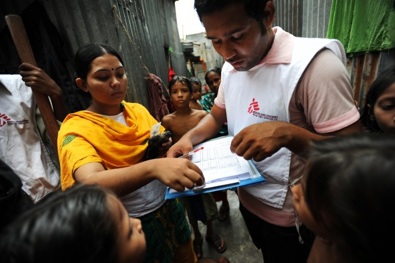 Two Doctors Without Borders health promoters look at a print-out of a diagram while learning to screen children within a community.