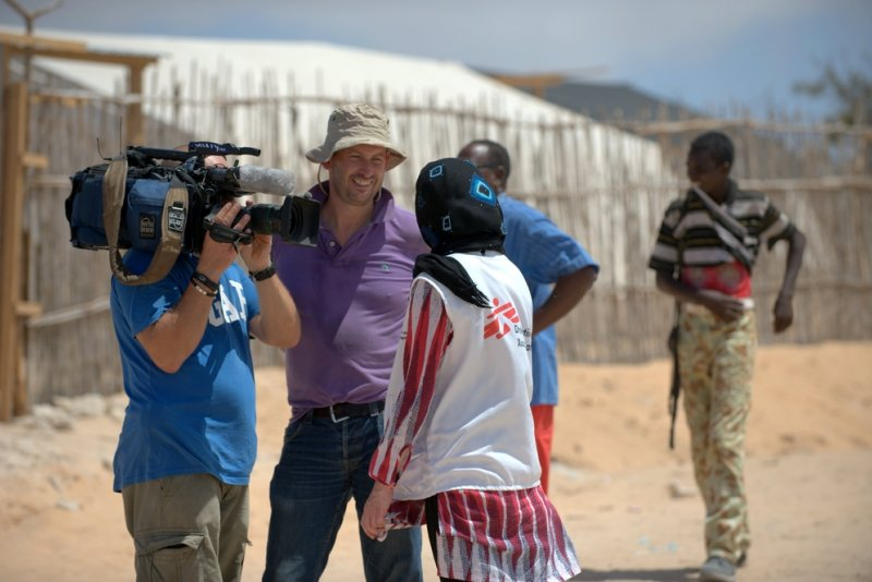 A Doctors Without Borders staff member being interviewed in the field in front of a video camera.