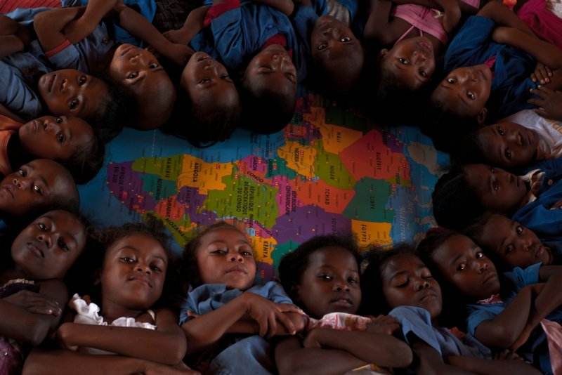 A group of school children lay together on a map of the world in Bekily, Madagascar.