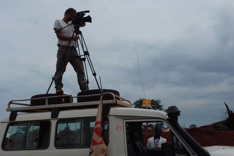 A Doctors Without Borders staff member standing on the roof of a vehicle and using video recording equipment.