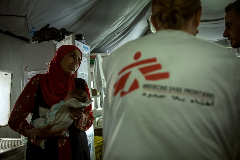 A Doctors Without Borders staff member consults a mother asking about the condition of her malnourished child.