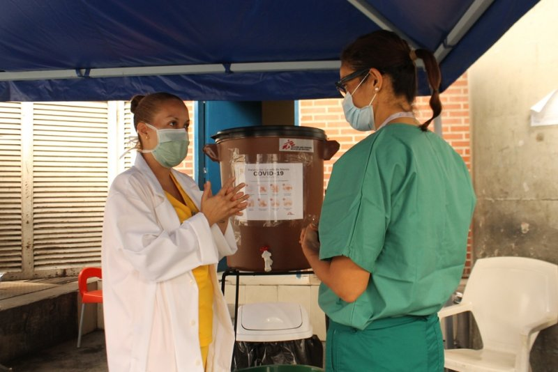 Two ladies are talking in a handwashing point