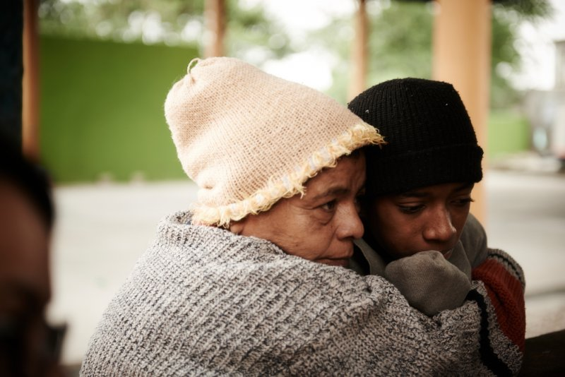A mother holds her son close to her in the Tenosique migrant shelter in Mexico.