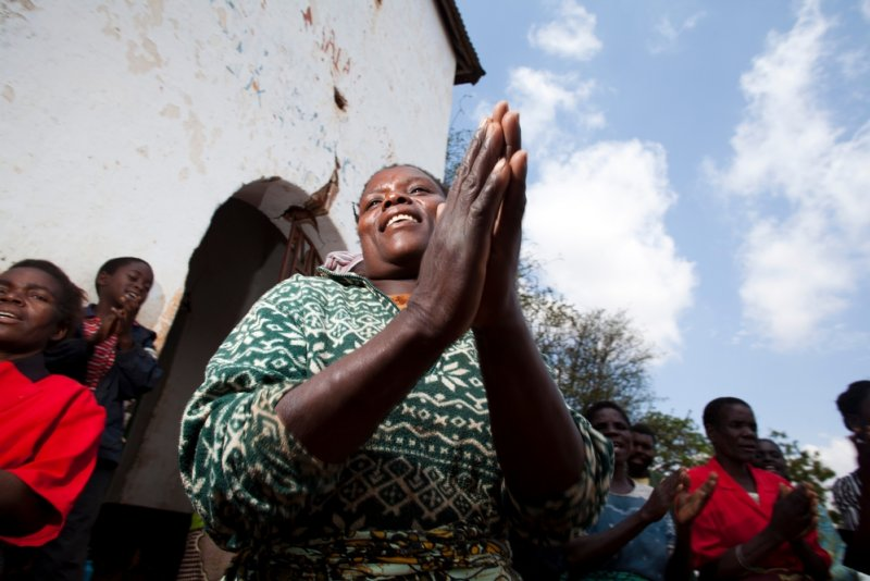 A patient in Malawi claps along with a group of peers.
