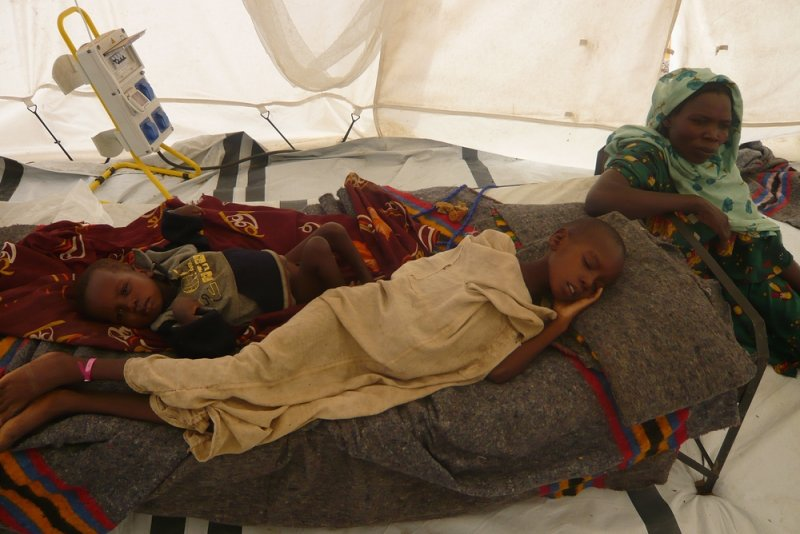 Internally displaced children rest on a cot in a makeshift shelter in Eastern Chad.