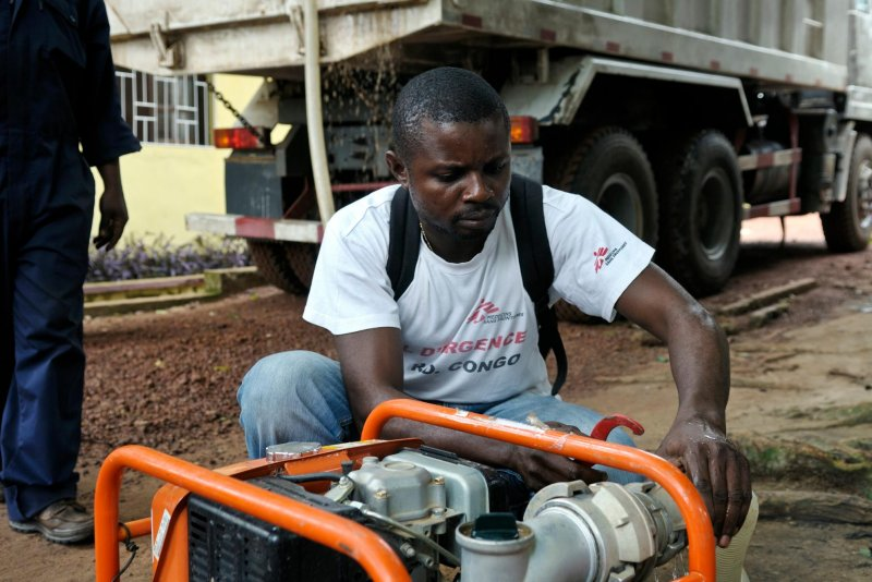 A Doctors Without Borders logistician pumping water from a well.