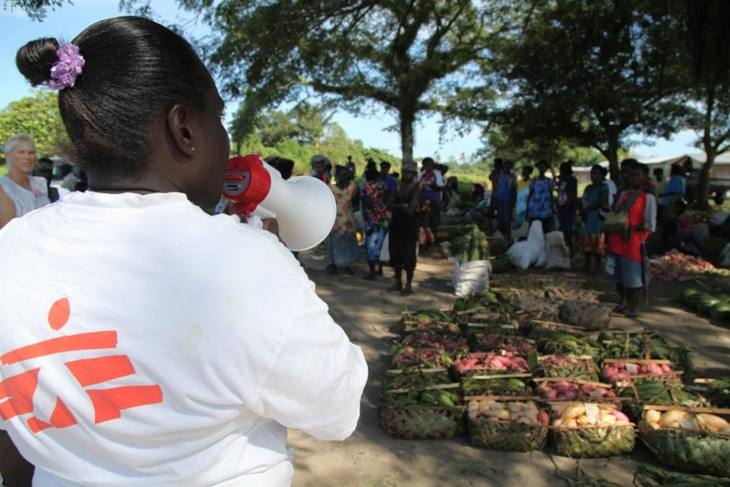A Doctors Without Borders staff member uses a megaphone to relay information to a crowd of people.