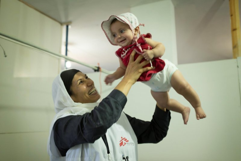 A Doctors Without Borders midwife holds up a child smiling gleefully.