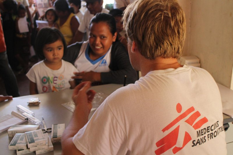 A Doctors Without Borders staff member consults a young patient and her mother in the Philippines.