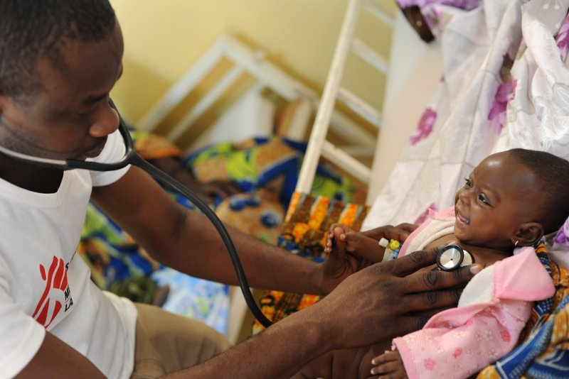 A Doctors Without Borders pediatrician uses a stethoscope to examine a smiling five-month old patient.