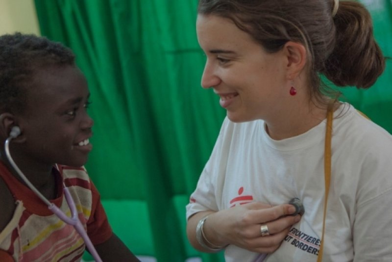 A Doctors Without Borders staff member lets a smiling patient check her heartbeat with a stethoscope.